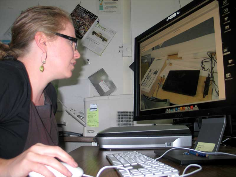 Click the image for a view of: Jessica, at her desk, looking at a picture of Nathaniel's work, next to her work, on his desk, in her studio.